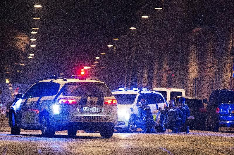 Police officers take cover behind their patrol cars on the streets of central Copenhagen on February 15, 2015, during attacks by a gunman