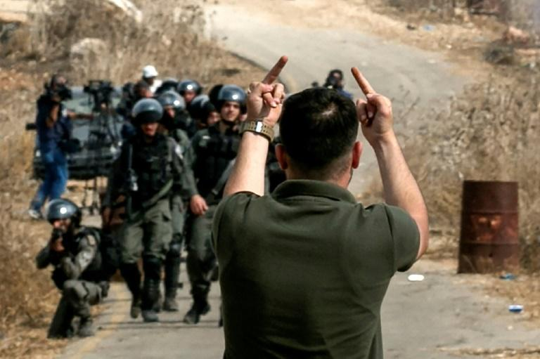 A Palestinian protester makes an insulting gesture to Israeli border guards during a protest against construction of an Israeli outpost near an Israeli settlement in the occupied West Bank