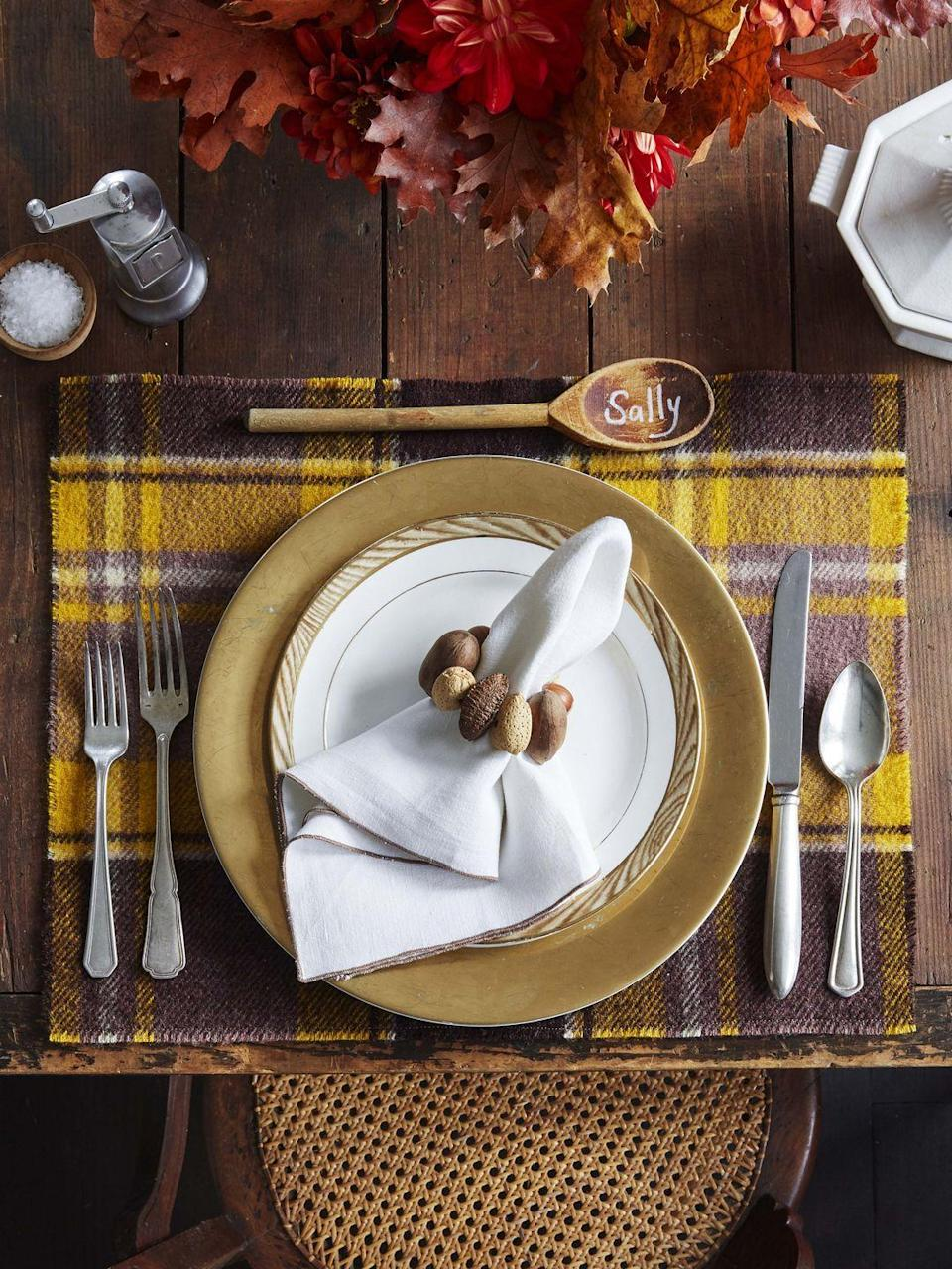 """<p>The hues of fall are on display in this warm and cozy table setting. <strong><br></strong></p><p><strong>To make:</strong> Start by cutting a vintage wool blanket into placemats. Drill holes in nuts and thread with wire or twine to create napkin rings. Finally pen guests names on new or vintage wooden spoons to create sweet place cards.</p><p><a class=""""link rapid-noclick-resp"""" href=""""https://www.amazon.com/NUTS-U-S-Hazelnuts-Artificial-Resealable/dp/B081ZLL331/ref=sr_1_1_sspa?tag=syn-yahoo-20&ascsubtag=%5Bartid%7C10050.g.2063%5Bsrc%7Cyahoo-us"""" rel=""""nofollow noopener"""" target=""""_blank"""" data-ylk=""""slk:SHOP NUTS"""">SHOP NUTS</a></p>"""