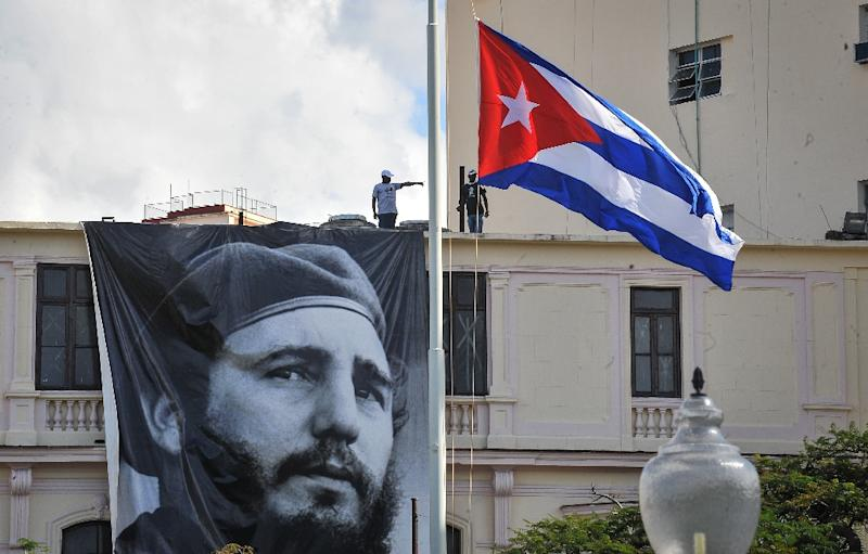 """A Cuban flag flutters at half mast near a banner depicting late Cuban revolutionary leader Fidel Castro, whom US President-elect called a """"brutal dictator"""" (AFP Photo/Yamil Lage)"""