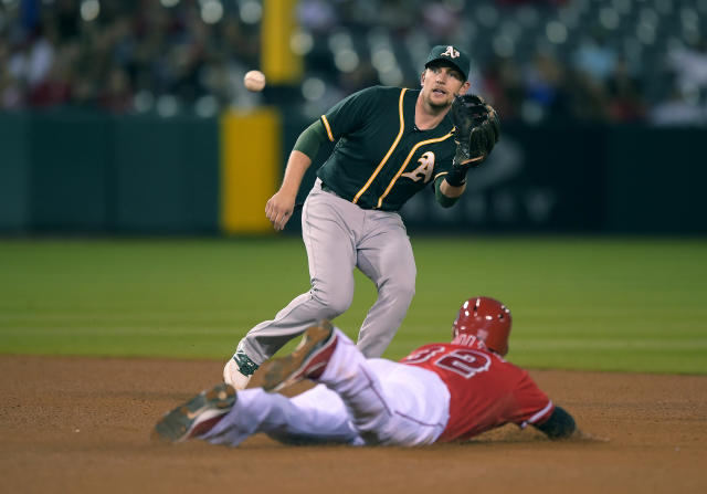 Los Angeles Angels' Josh Hamilton, below, steals second as Oakland Athletics shortstop Jed Lowrie takes a late throw from first during the fourth inning of a baseball game, Tuesday, June 10, 2014, in Anaheim, Calif. (AP Photo/Mark J. Terrill)