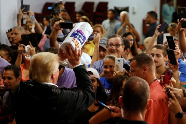 President Donald Trump tosses rolls of paper towels to people at a hurricane relief distribution center at Calvary Chapel in San Juan, P.R., on Oct. 3. (Reuters/Jonathan Ernst)