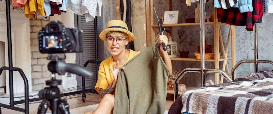 Young woman fashion blogger influencer wearing hat and eyeglasses sitting on fluffy carpet at urban stylish apartment recording video vlog on digital camera telling clothing tips positive