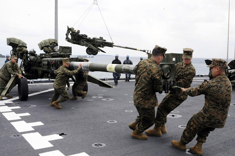 FILE - In this Feb. 2, 2012 file photo released by U.S. Navy, U.S. Marines assigned to the 31st Marine Expeditionary Unit haul a 155 mm Howitzer onto the flight deck of the forward-deployed amphibious dock landing ship USS Germantown in Okinawa, Japan, when the ship pulled into Okinawa to embark the Marines in preparation of exercise Cobra Gold 2012. About 9,000 U.S. Marines stationed on the Japanese island of Okinawa will be moved to the U.S. territory of Guam and other locations in the Asia-Pacific, including Hawaii, under a U.S.-Japan agreement announced Thursday, April 26. (AP Photo/U.S. Navy, Mass Communication Specialist 1st Class Johnie Hickmon, File)