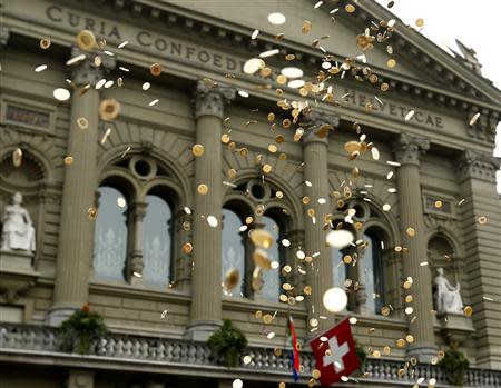 Five cent coins are pictured in the air in front of the Federal Palace during an event organised by the Committee for the initiative Grundeinkommen in Bern