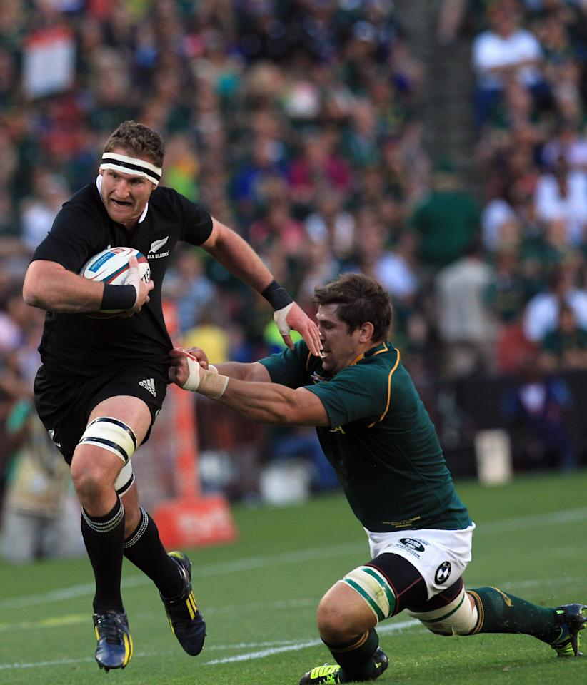 New Zealand's Kieran Read, left, breaks away from a tackle by South Africa's Willem Alberts, right, during their Rugby Championship match at Ellis Park Stadium in Johannesburg, South Africa, Saturday, Oct. 5, 2013. (AP Photo/Themba Hadebe)