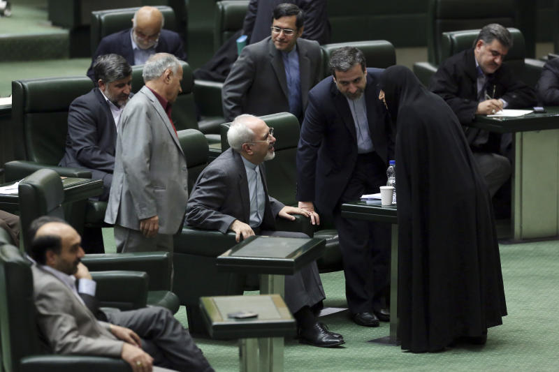 Iranian Foreign Minister Mohammad Javad Zarif, center, talks with members of the parliament as he arrives in Tehran, Iran, Wednesday, Nov. 27, 2013. Hard-line Iranian politicians publicly criticized the deal reached in Geneva last week over the Islamic Republic's nuclear program, an agreement that has largely been welcomed by Iranians. (AP Photo/Ebrahim Noroozi)