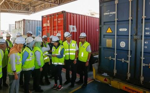Malaysian officials inspect a container before it is returned to its country of origin - Credit: AFP