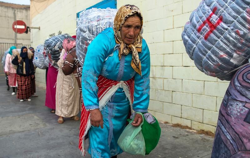 Female Moroccan porters carry huge bundles of goods strapped by rope to their backs to transport from Spain's North African exclave of Ceuta into Morocco (AFP Photo/FADEL SENNA)
