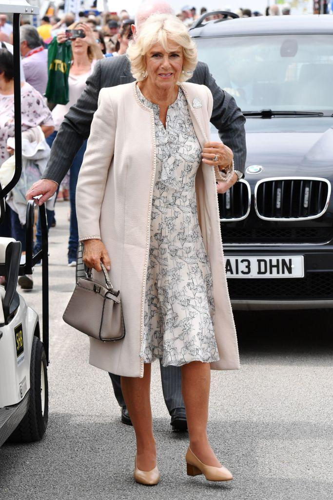<p>The Duchess of Cornwall wore a printed ivory dress, a light pink coat, and carried a gray purse while attending the Royal Cornwall Show in Wadebridge, England.</p>
