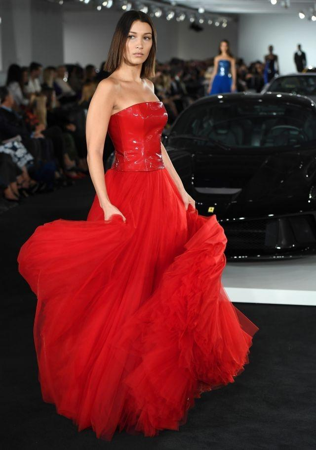Bella Hadid swishes a bright red dress in the Ralph Lauren runway show at New York Fashion Week
