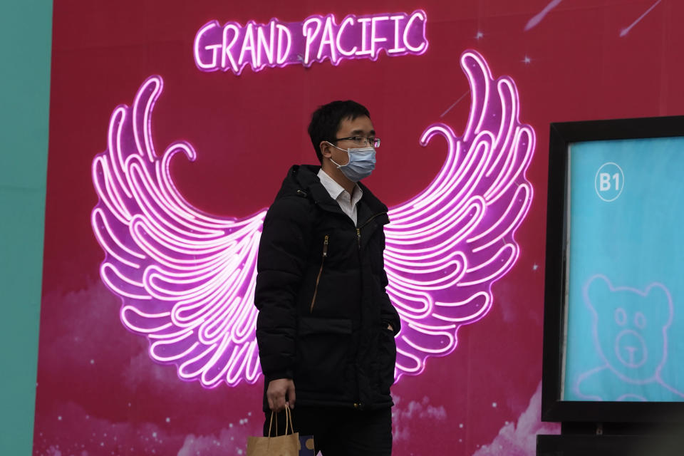 A man wearing a mask to protect from the coronavirus passes by neon lights along a retail street in Beijing Tuesday, March 2, 2021. The state of the world's second largest economy takes precedence among the myriad issues presented by Premier Li Keqiang in his address at the National People's Congress opening session to take place on Friday, March 5. 2021. (AP Photo/Ng Han Guan)