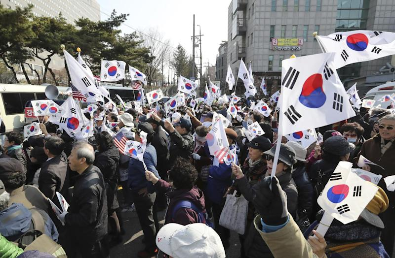 "Supporters of South Korean ousted President Park Geun-hye wave flags outside of a prosecutors' office in Seoul, South Korea, Tuesday, March 21, 2017. Park said she was ""sorry"" to the people as she arrived Tuesday at a prosecutors' office for questioning over a corruption scandal that led to her removal from office. (AP Photo/Lee Jin-man)"