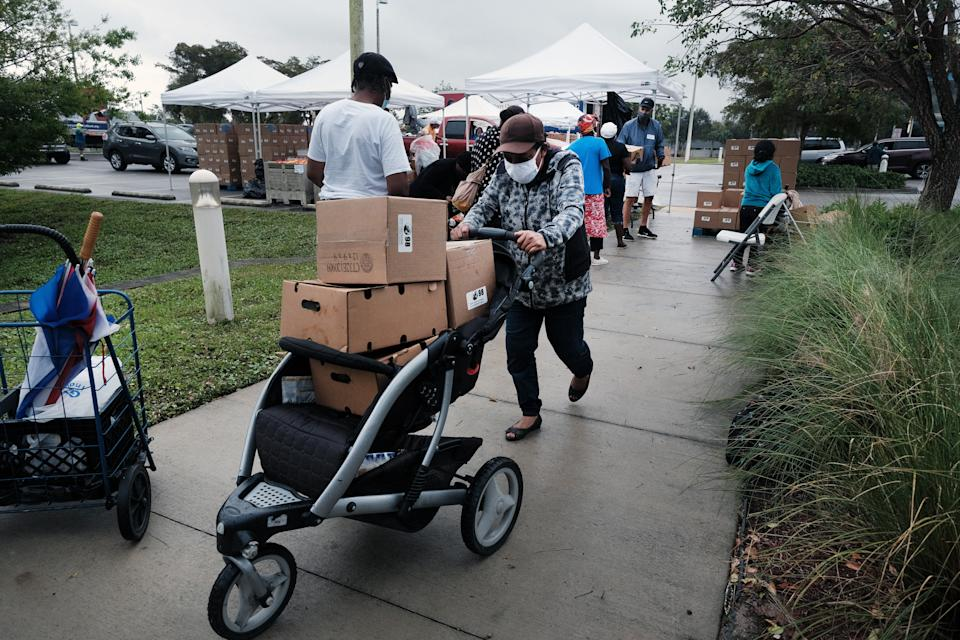IMMOKALEE, FLORIDA - FEBRUARY 16: Food is distributed during a mobile food pantry in the agricultural community of Immokalee on February 16, 2021 in Immokalee, Florida. The Harry Chapin Food Bank has weekly distributions in the town which has a poverty rate of over 40% and has a population made up primarily of agricultural workers. The mobile food pantry gives out food packages for over 800 families after seeing a surge in need since the Covid-19 outbreak. (Photo by Spencer Platt/Getty Images)