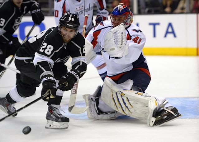Los Angeles Kings center Jarret Stoll, left, goes after a rebound as Washington Capitals goalie Jaroslav Halak, of Slovakia, watches during the second period of an NHL hockey game, Thursday, March 20, 2014, in Los Angeles. (AP Photo/Mark J. Terrill)