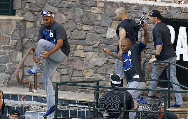 Los Angeles Dodgers players jump into the pool at Chase Field after the Dodgers clinched the NL West title with a 7-6 win over the Arizona Diamondbacks in a baseball game Thursday, Sept. 19, 2013, in Phoenix. (AP Photo/Ross D. Franklin)