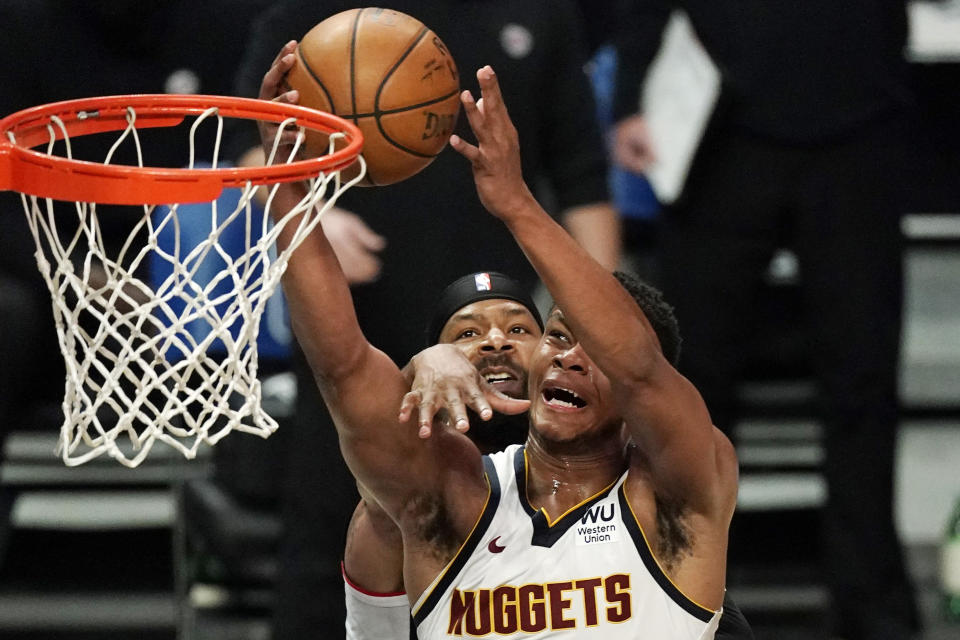 Denver Nuggets guard PJ Dozier, right, shoots as Los Angeles Clippers forward Marcus Morris Sr. defends during the second half of an NBA basketball game Saturday, May 1, 2021, in Los Angeles. (AP Photo/Mark J. Terrill)