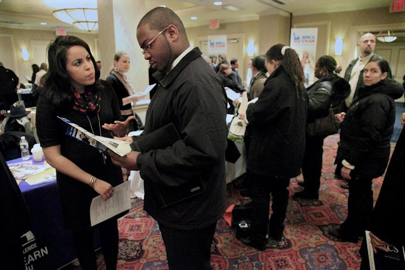 Daniela Silvero, left, an admissions officer at ASA College, discusses job opportunities with Patrick Rosarie, who is seeking a job in IT, during JobEXPO's job fair on Wednesday, Jan. 25, 2012 in New York.  The number of people seeking unemployment benefits rose last week, after falling to a nearly four-year low the previous week.  (AP Photo/Bebeto Matthews)