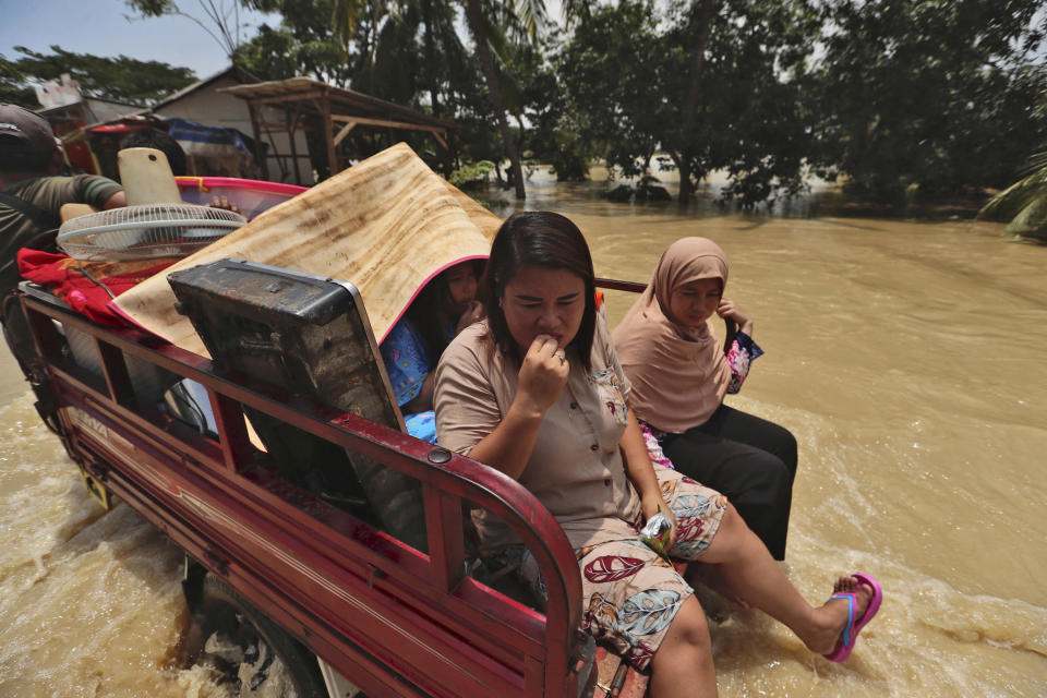 Indonesian women sit on the back of a three-wheeled motorcycle carrying their belongings to high ground at an area flooded after the embankment of Citarum River burst, in Bekasi, Indonesia, Monday, Feb. 22, 2021. Heavy rains caused rivers to burst their banks in the region sending muddy water into residential and commercial areas, inundating thousands of homes. (AP Photo/Achmad Ibrahim)