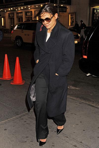 Katie Holmes is prepared for the cold New York City weather all bundled up in a long trench pea coat, wide-legged trousers, chic heels and a white top. In typical Hollywood style, she sports sunnies even at night. Picture by: Demis Maryannakis / Splash News