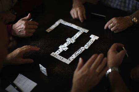 Pensioners play dominoes at a seniors centre during the International Day of Older Persons in Ronda