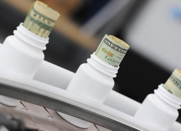 Plain white bottles on a manufacturing line, with rolled twenty dollar bills sticking out the top of them.