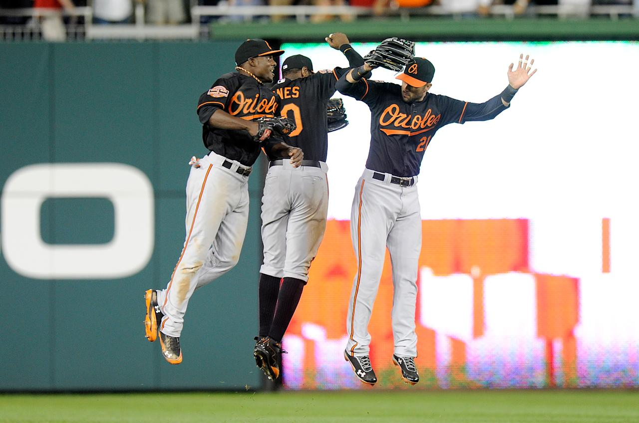 WASHINGTON, DC - MAY 18:  Xavier Avery #13, Adam Jones #10 and Nick Markakis #21 of the Baltimore Orioles celebrate after a 2-1 victory against the Washington Nationals at Nationals Park on May 18, 2012 in Washington, DC.  (Photo by Greg Fiume/Getty Images)