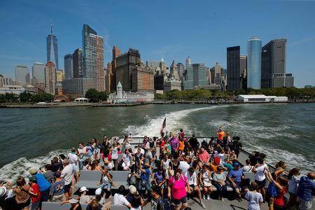 FILE PHOTO: People take the ferry to visit the Liberty State Island, with Lower Manhattan in the background, in New York, U.S., August 17, 2017. REUTERS/Eduardo Munoz/File Photo