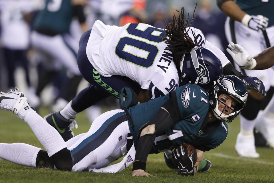 Seattle's Jadeveon Clowney (90) hits Eagles quarterback Carson Wentz (11) during the first half their wild-card playoff game on Sunday. (AP Photo/Julio Cortez)