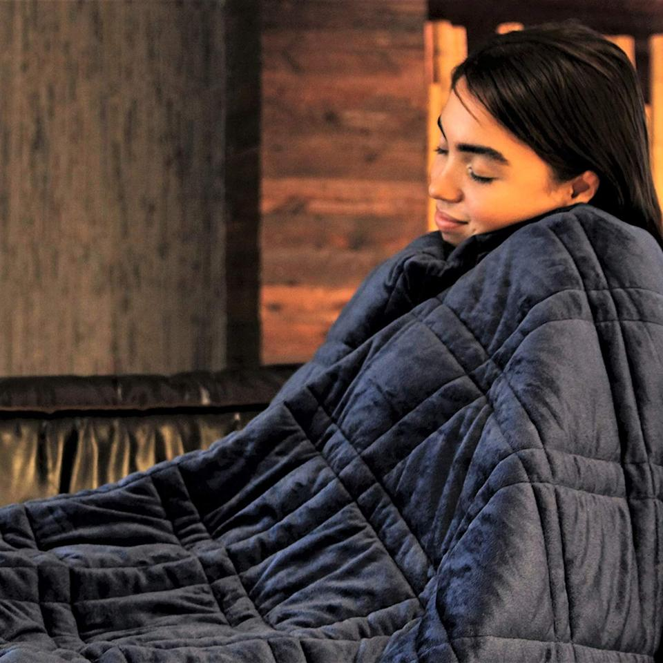 """<p>We're getting cozy in this <a href=""""https://www.popsugar.com/buy/Pine-River-Ultra-Plush-Weighted-Blanket-557398?p_name=Pine%20and%20River%20Ultra%20Plush%20Weighted%20Blanket&retailer=amazon.com&pid=557398&price=50&evar1=fit%3Aus&evar9=47315539&evar98=https%3A%2F%2Fwww.popsugar.com%2Ffitness%2Fphoto-gallery%2F47315539%2Fimage%2F47315545%2FPine-River-Ultra-Plush-Weighted-Blanket&list1=shopping%2Camazon%2Cstress%20relief%2Canxiety%2Chealthy%20living&prop13=mobile&pdata=1"""" rel=""""nofollow"""" data-shoppable-link=""""1"""" target=""""_blank"""" class=""""ga-track"""" data-ga-category=""""Related"""" data-ga-label=""""https://www.amazon.com/Pine-River-Ultra-Weighted-Blanket/dp/B07JPJYFZL/ref=sr_1_25?crid=3P9Y206QPK7FC&amp;keywords=weighted+blanket&amp;qid=1584467282&amp;sprefix=weighted+b%2Caps%2C224&amp;sr=8-25"""" data-ga-action=""""In-Line Links"""">Pine and River Ultra Plush Weighted Blanket</a> ($50).</p>"""