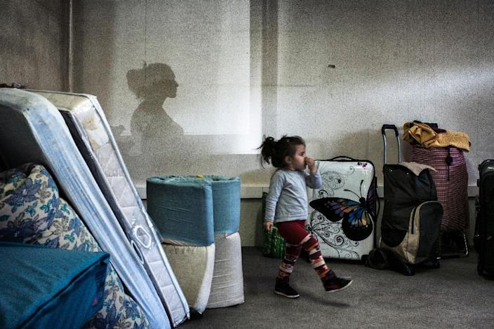 A girl walks amongst bags and mattresses as Eastern European migrants wait to temporarily settle in a locale in Decines after staying in buildings belonging to the army and the diocese of Lyon, on April 21, 2015 (AFP Photo/Jeff Pachoud)