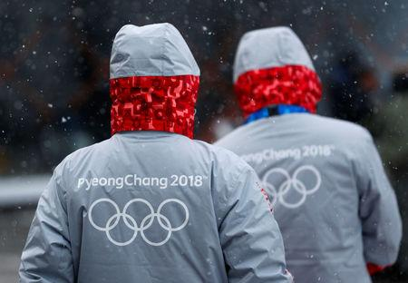 Volunteers for the upcoming 2018 Pyeongchang Winter Olympic Games walk in Pyeongchang