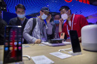 People wearing face masks to protect against the spread of the coronavirus look at smartphones and consumer electronics from Chinese technology firm Huawei at the PT Expo in Beijing, Wednesday, Oct. 14, 2020. Chinese leaders are shifting focus from the coronavirus back to long-term goals of making China a technology leader at this year's highest-profile political event, the meeting of its ceremonial legislature, amid tension with Washington and Europe over trade, Hong Kong and human rights. (AP Photo/Mark Schiefelbein)