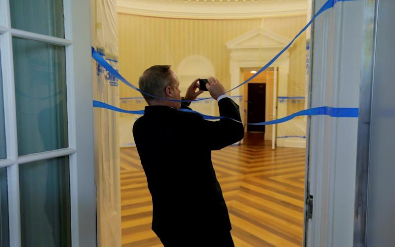 Former White House Press Secretary Spicer wraps himself in tape as he takes photos of the Oval Office emptied of all furniture, carpet and other decor during renovations at the White House in Washington - REUTERS