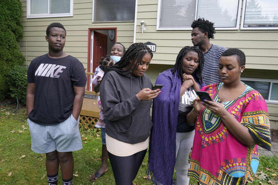 From left, Kevin Mugisha, Guillin Mugabo Toto, Sada Batamuriza, Kevine Uwase, Patrick Bizima, and Emmerence Mugeni stand in the yard of the home they share with their father, Wednesday, Oct. 14, 2020, and look at photos of their mother, Ziporah Nyirahimbya, who is in Uganda and has been unable so far to join them in the U.S. For decades, America admitted more refugees annually than all other countries combined, but that reputation has eroded during Donald Trump's presidency as he cut the number of refugees allowed in by more than 80 percent. (AP Photo/Ted S. Warren)