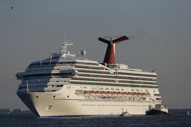 FILE - In this Feb. 14, 2013 file photo the cruise ship Carnival Triumph is towed into Mobile Bay near Dauphin Island, Ala. The Triumph, which has been docked in Alabama since an engine room fire left it disabled for days in the Gulf of Mexico, broke away from its mooring in a Mobile, Ala. shipyard on Wednesday, April 3, 2013. The U.S. Coast Guard tweeted Wednesday afternoon that high winds were likely to blame. (AP Photo/Dave Martin, File)