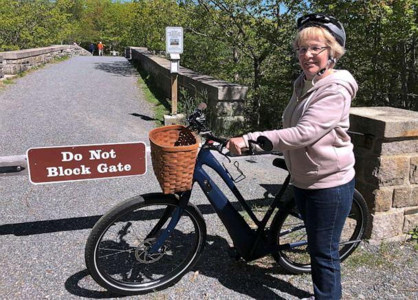 PHOTO: In this June 8, 2019 file photo, Janice Goodwin stands by her electric-assist bicycle at a gate near the start of the carriage path system where bikes such as her are banned inside Acadia National Park, in this photo June 8, 2018. (David Sharp/AP Photo)