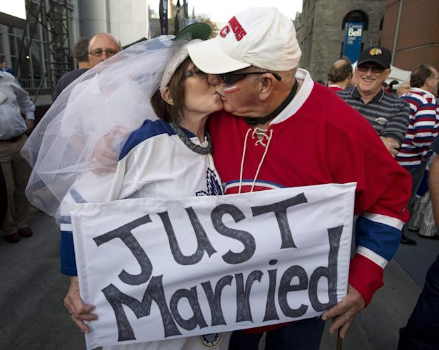 Newlyweds Martha Hartland-Mills and Paul Hart, who were married Tuesday in Nova Scotia, kiss as they take part in pregame festivities before the season-opening NHL hockey game between the Toronto Maple Leafs and the Montreal Canadiens, Tuesday, Oct. 1, 2013, in Montreal. (AP Photo/The Canadian Press, Ryan Remiorz)