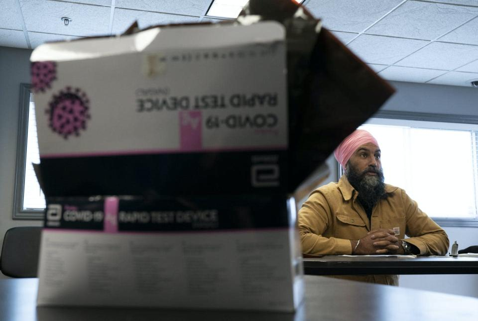 A COVID-19 rapid test package in the foreground, with NDP leader Jagmeet Singh seated at a table in the background
