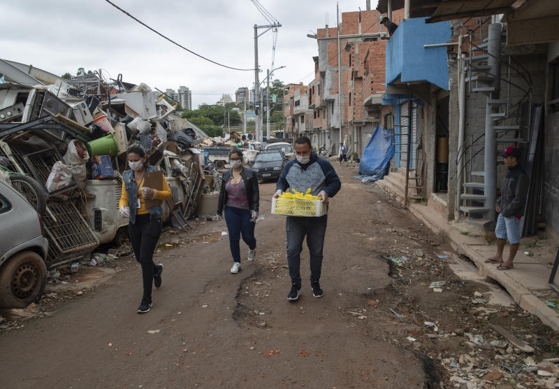 Volunteers carry meals to be distributed to residents in the Paraisopolis slum during a quarantine imposed by the state government to help stop the spread of the new coronavirus in Sao Paulo, Brazil, Wednesday, April 8, 2020. (AP Photo/Andre Penner)