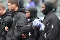 Colorado Rockies' Eric Young Jr., center, and others try to keep warm in below-freezing weather before the first baseball game of a doubleheader against the Atlanta Braves, Tuesday, April 23, 2013, in Denver. The Braves won 4-3. (AP Photo/Barry Gutierrez)