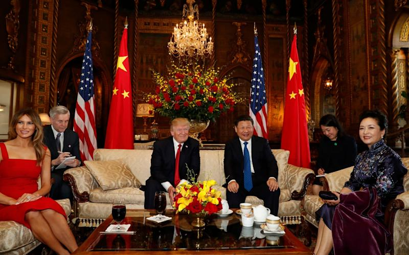 President Donald Trump and Chinese President Xi Jinping, with they wives, first lady Melania Trump, left, and Chinese first lady Peng Liyuan, right, pose for photographers before dinner at Mar-a-Lago - AP