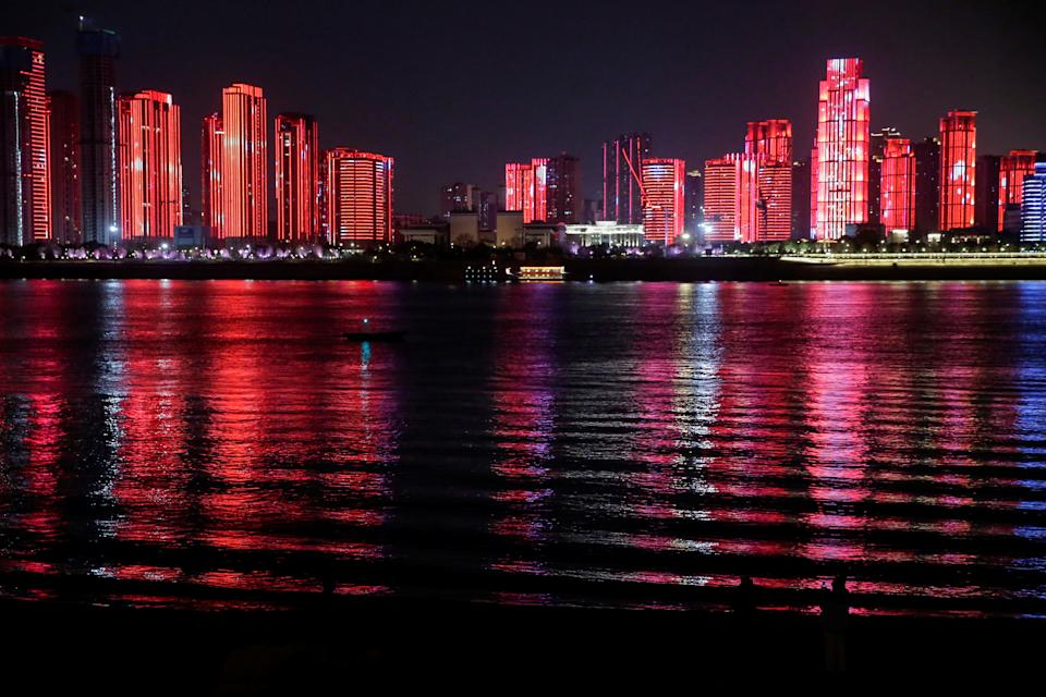 A light show is projected on buildings by a river on New Year's Eve in Wuhan (Reuters)