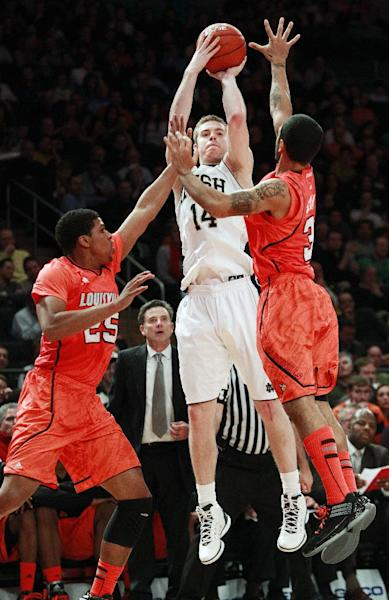 Notre Dame's Scott Martin (14) shoots over Louisville's Wayne Blackshear (25) and Peyton Siva (3) during the first half of an NCAA college basketball game in the semifinals of the Big East Conference tournament in New York, Friday, March 9, 2012. (AP Photo/Frank Franklin II)