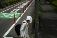 An elderly woman walks with a small towel over her head to shield from the sun ahead the 2020 Summer Olympics, Wednesday, July 14, 2021, in Tokyo. (AP Photo/Jae C. Hong)