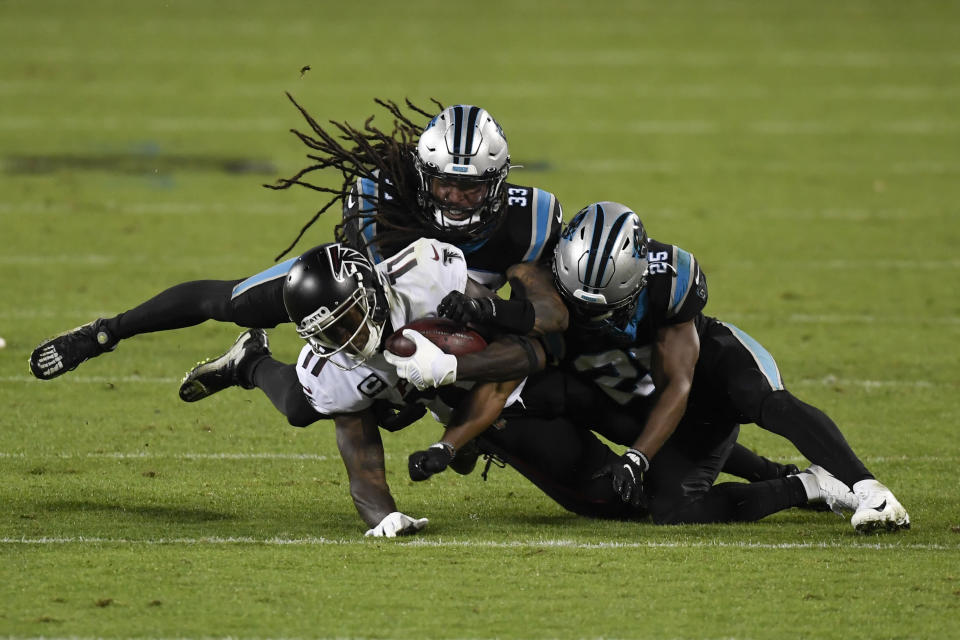 Atlanta Falcons wide receiver Julio Jones I is tackled by Carolina Panthers free safety Tre Boston and cornerback Troy Pride during the second half of an NFL football game Thursday, Oct. 29, 2020, in Charlotte, N.C. (AP Photo/Mike McCarn)