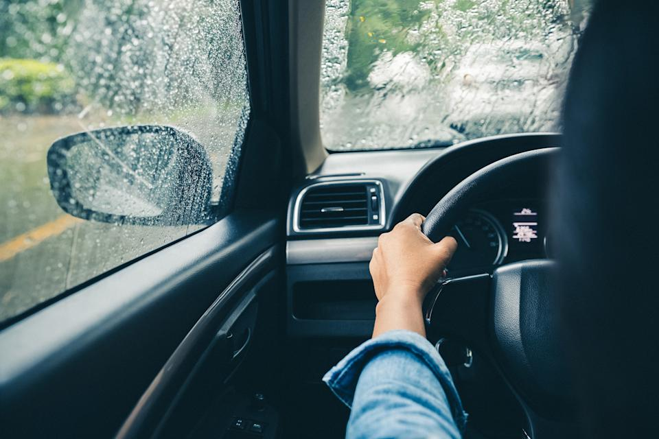 closeup driver's hands on steering wheel driving on rainy day