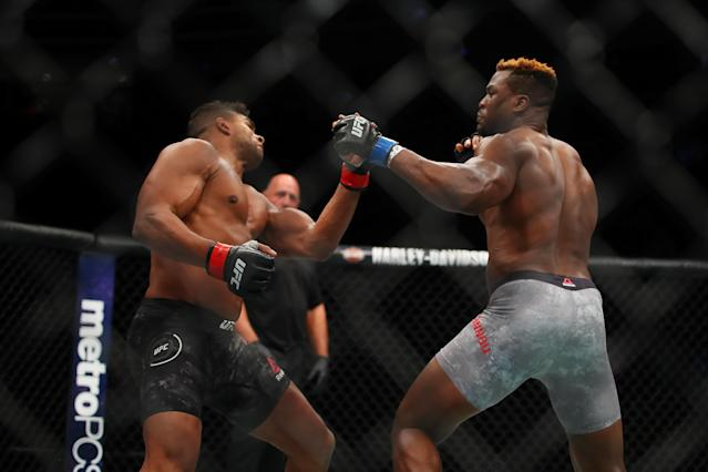 Francis Ngannou (R) lands a left hook Saturday that KOs Alistair Overeem in the first round of their bout at UFC 218 in Detroit. (Getty Images)