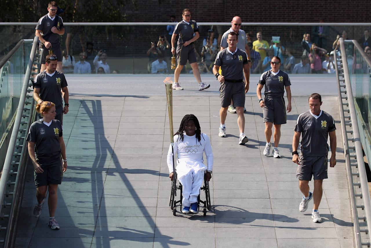 LONDON, ENGLAND - JULY 26:  Wheelchair basketball player Adedoyin Adepitan (C) carries the Olympic flame over Millennium Bridge in front of St Paul's Cathedral during Day 69 of the London 2012 Olympic Torch Relay on July 26, 2012  in London, England. The Olympic flame is making its way through the capital on the penultimate day of its journey around the UK before arriving in the Olympic Stadium on Friday evening for the Olympic games' Opening Ceremony.  (Photo by Oli Scarff/Getty Images)
