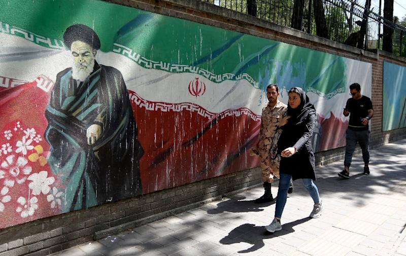People walk past a mural depicting the founder of the Islamic republic Ayatollah Ruhollah Khomeini and painted on the walls surrounding the former US embassy in the Iranian capital on June 22, 2019 amid an escalation between Washington and Tehran (AFP Photo/ATTA KENARE)